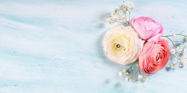 Schöner rosa butterblumenrahmen auf türkisholz