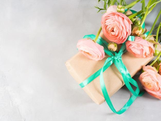 Schöner rosa ranunkel blüht blumenstrauß und geschenkbox. valentinstag mutter. hochzeits-geburtstagsgeschenk