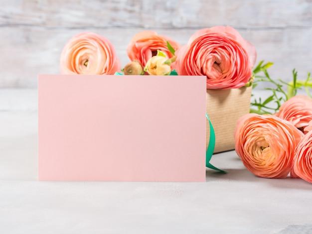 Schöner rosa ranunkel blüht blumenstrauß und geschenkbox. valentinstag mutter. hochzeitsgeburtstagsgeschenk-grußkarte