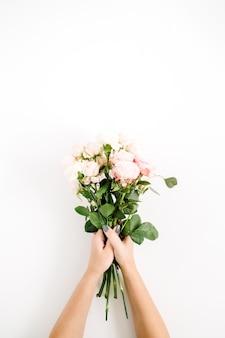 Schöner rosa rosenblumenstrauß in der mädchenhand lokalisiert auf weißem hintergrund. flache lage, ansicht von oben