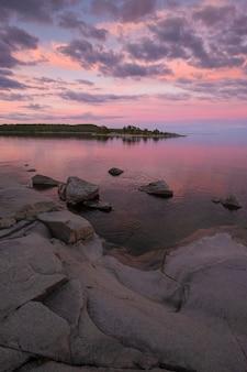 Schöner rosa sonnenuntergang am ladogasee in karelien, russland im nationalpark ladoga skerries im sommer. naturlandschaft mit wasserfelsen, steininseln und wald in ufernähe