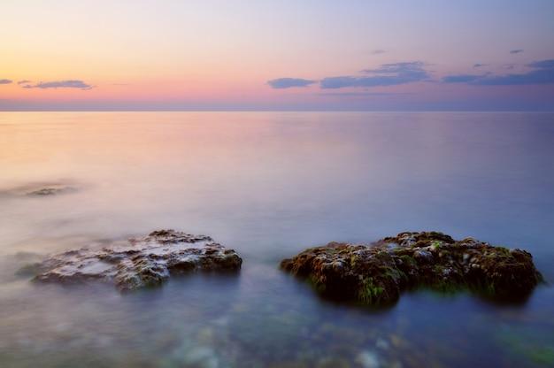 Schöner rosa sonnenuntergang und wassersteine über felsiger küste des schwarzen meeres auf der krim am sommertag.