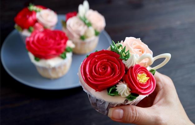 Schöner rosenstrauß, der cupcake in der hand der frau mit teller der verschwommenen cupcakes im hintergrund bereift