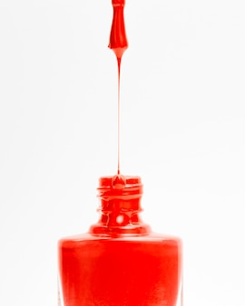 Schöner roter farbiger nagellack, der von der bürste in flasche auf weißem hintergrund tropft