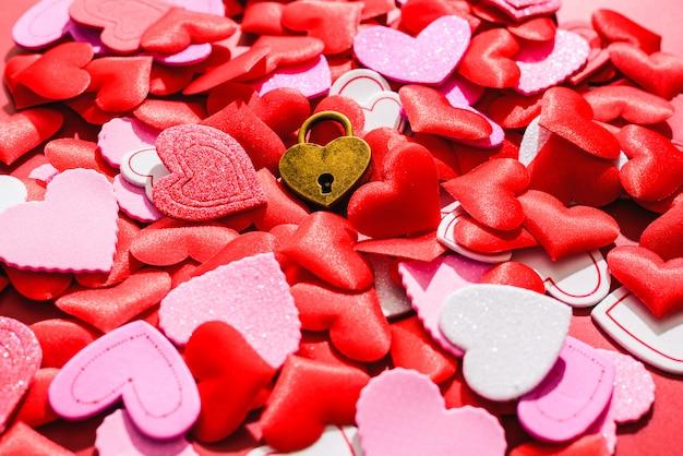 Schöner roter hintergrund mit herzen und einem liebesvorhängeschloss für valentinsgrüße.