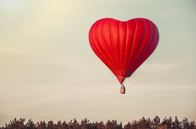 Schöner roter luftballon in form von herzen fliegt hoch in den himmel romantische verabredungsgeschenkreise auf