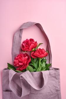 Schöner roter pfingstrosenblumenstrauß in baumwoll-öko-einkaufstasche über rosafarbenem hintergrund, draufsicht, kopienraum, flach. valentinstag, muttertag hintergrund.