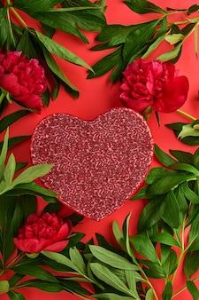 Schöner roter pfingstrosenblumenstrauß mit roter geschenkbox über rotem hintergrund, draufsicht, kopienraum, flach. valentinstag, muttertag hintergrund.