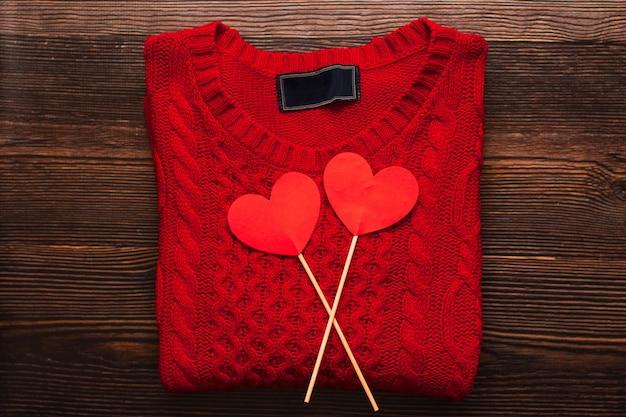 Schöner roter pullover und zwei rote herzen auf stöcken lokalisiert auf einem dunklen hölzernen hintergrund. draufsicht auf flatlay. valentinstag und weihnachtskonzept. copyspace, mode.