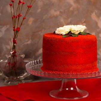 Schöner roter samtgeburtstagskuchen verziert mit weißen rosen
