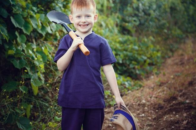 Schöner rothaariger junge mit sommersprossen hilft im garten. die idee und das konzept der frühen schulbildung für die arbeit im garten der kinder
