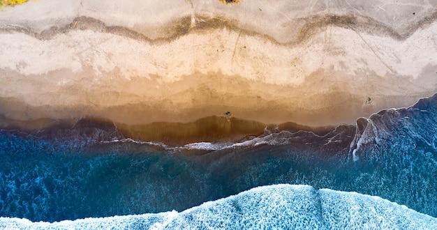 Schöner sandstrand und meer mit wellen von oben gesehen