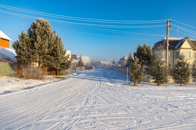 Schöner schneebedeckter baum auf dem hintergrund eines hauses, moderne winterdorflandschaft des winters nahe kemerowo, sibirien, russland