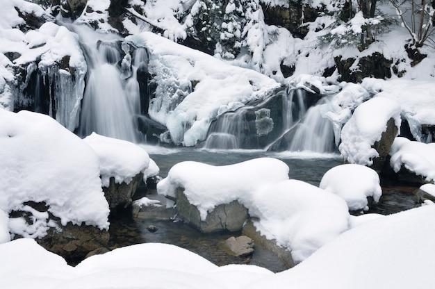 Schöner schneebedeckter wasserfall, der in den bergen fließt. winterlandschaft. schneebedeckte bäume