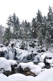 Schöner schneebedeckter wasserfall, der in den bergen fließt