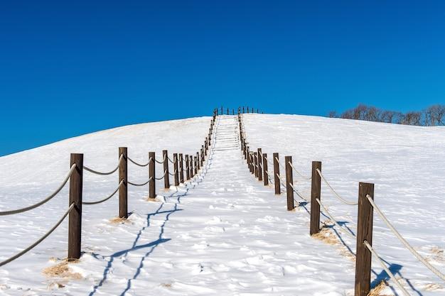 Schöner schneetreppenweg und blauer himmel mit schneebedeckter winterlandschaft