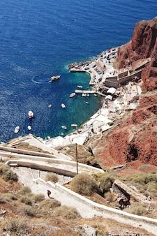 Schöner schuss der alten gebäude nahe der klippe im ufer mit booten im ozean