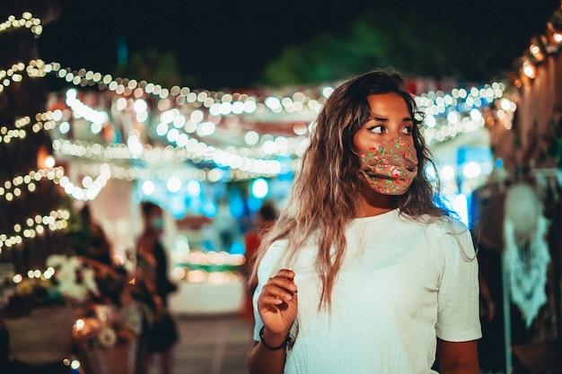 Schöner schuss der gebräunten europäischen frau, die eine blumenmaske an einem vergnügungspark trägt