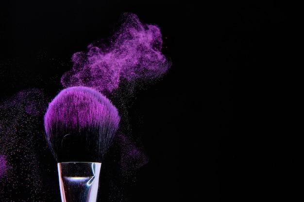 Schöner schuss der make-up-bürste lokalisiert auf schwarz