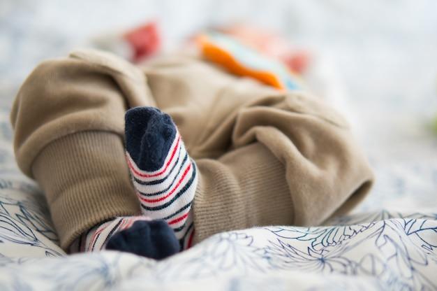 Schöner schuss der niedlichen kleinen füße eines babys, das auf einem bett liegt