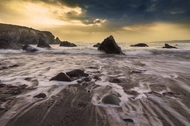 Schöner schuss der ozeanwellen, die während des sonnenuntergangs am felsigen ufer abstürzen