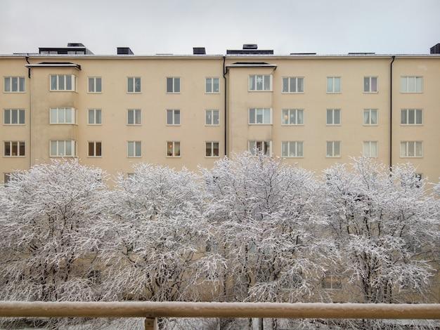 Schöner schuss des gelben gebäudes und der bäume, die während des winters mit schnee bedeckt werden