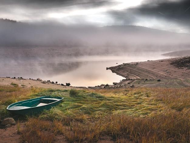 Schöner schuss des grünen bootes auf einem grasbewachsenen hügel nahe dem meer mit einem nebel