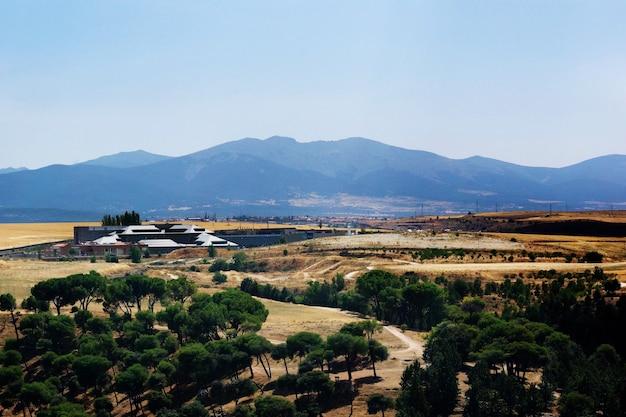 Schöner schuss des grünen und gelben tals mit bergen im hintergrund in segovia, spanien