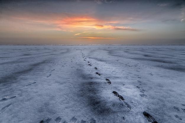 Schöner schuss des sonnenuntergangs über dem strand mit fußspuren, die zum meer führen