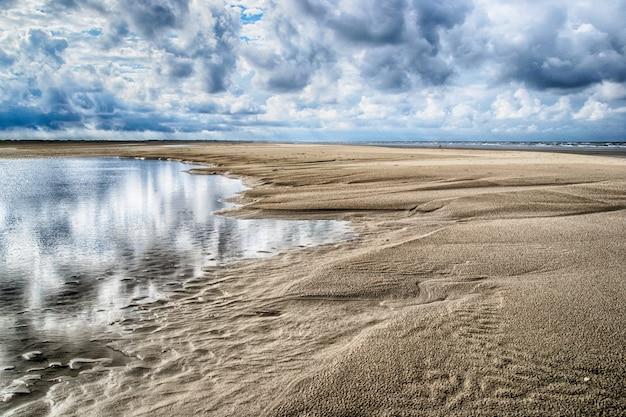 Schöner schuss des verlassenen sandigen ufers des ozeans unter dem bewölkten himmel