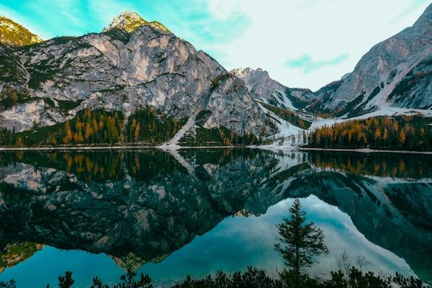 Schöner schuss des wassers, das die gelben und grünen bäume nahe den bergen mit einem blauen himmel reflektiert