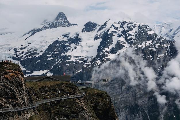 Schöner schuss einer brücke nahe den bergen, die mit schnee gefüllt werden