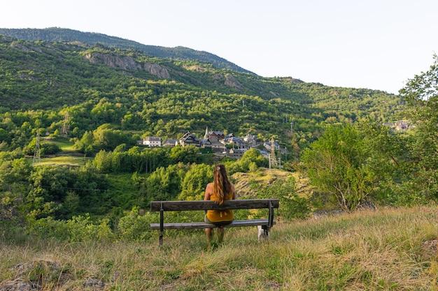 Schöner schuss einer frau, die auf der bank sitzt, die eine berglandschaft gegenüberstellt