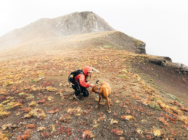 Schöner schuss einer frau, die einen hund auf einem berg mit einem weißen himmel streichelt