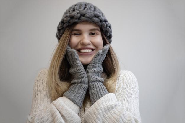 Schöner schuss einer hübschen fröhlichen frau, die einen gestrickten grauen hut und handschuhe trägt