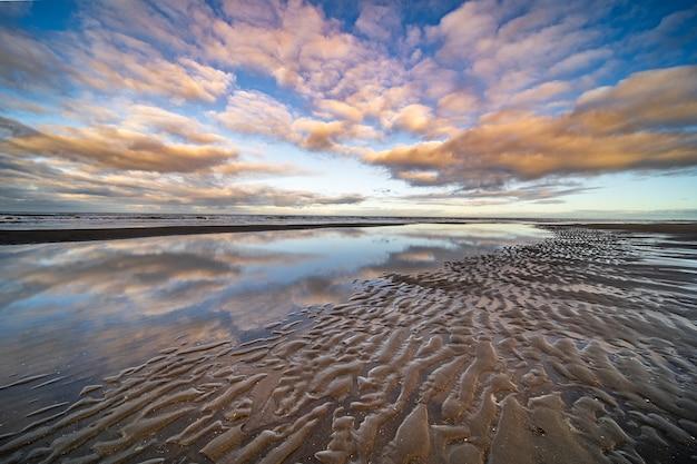 Schöner schuss einer nassen küste unter einem blauen himmel