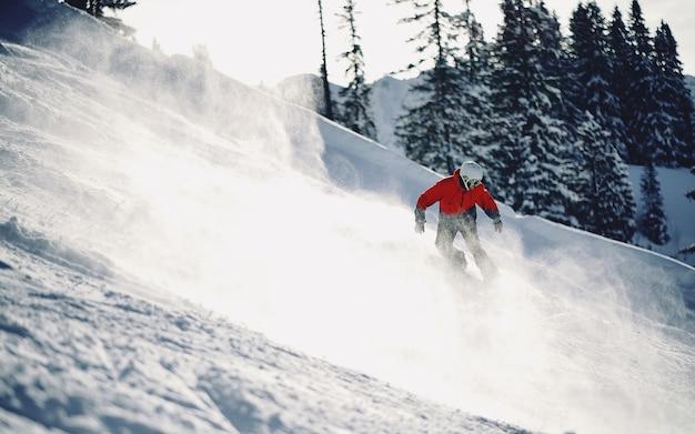 Schöner schuss einer person mit roter jacke, die den schneebedeckten berg mit unscharfem hintergrund abfährt
