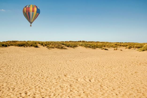 Schöner schuss einer sandigen landschaft mit einem fliegenden heißluftballon