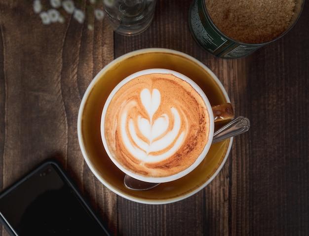 Schöner schuss einer tasse cappuccino mit einem weißen herzmuster auf einem holztisch