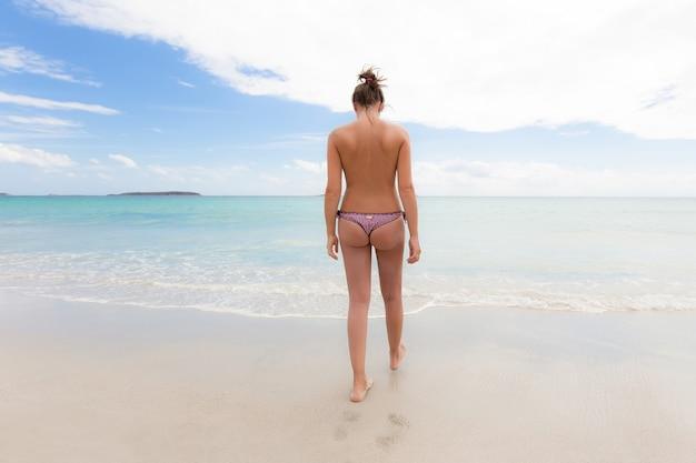 Schöner schuss einer topless frau, die auf dem strand geht