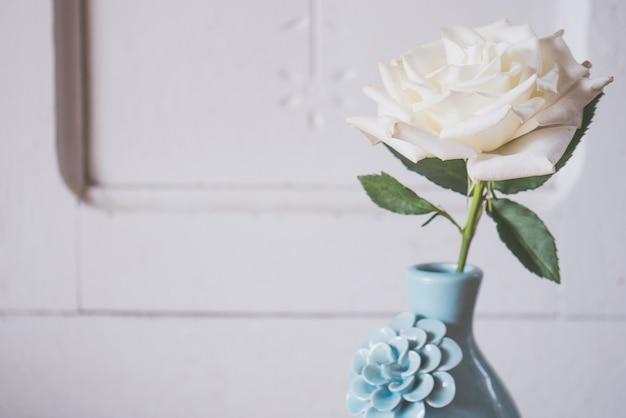Schöner schuss einer weißen rose in einer blauen vase auf einem weißen hintergrund