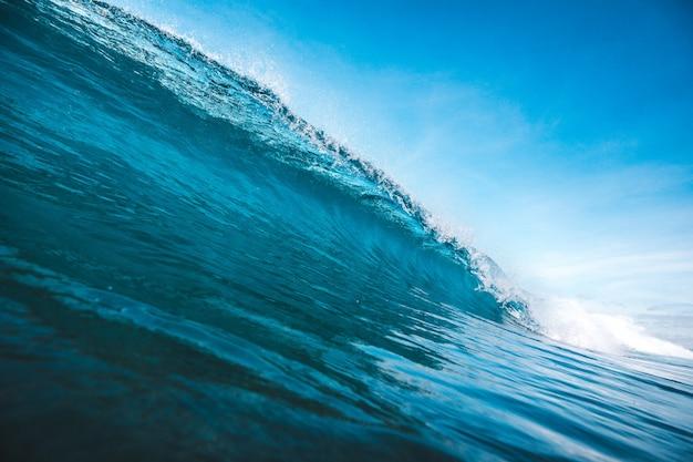 Schöner schuss einer welle, die form unter dem klaren blauen himmel nimmt, der in lombok, indonesien gefangen genommen wird