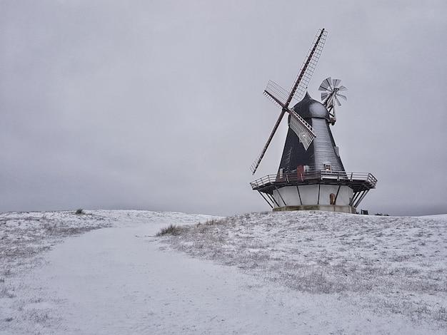 Schöner schuss einer windmühle in der mitte eines winterfeldes