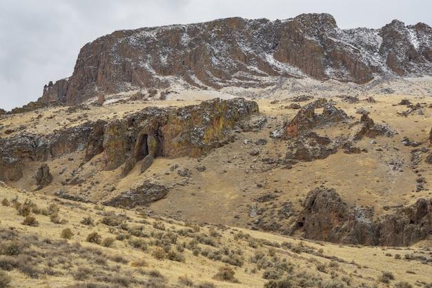 Schöner schuss einer wüste mit einem schneebedeckten berg in der ferne und einem bewölkten himmel