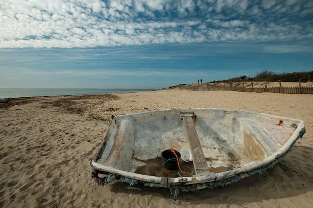 Schöner schuss eines alten fischerboots am strand an einem sonnigen tag