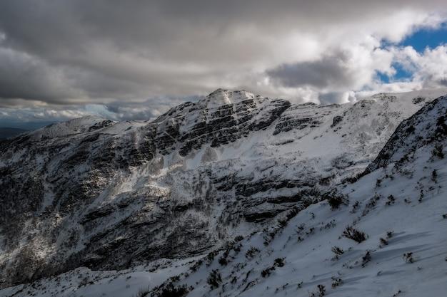 Schöner schuss eines berges bedeckt mit schnee und dicken wolken, die den blauen himmel bedecken
