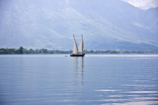 Schöner schuss eines bootes, das auf dem wasser mit bewaldeten bergen segelt