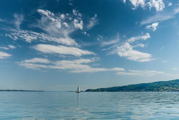 Schöner schuss eines bootes, das in einem ruhigen meer mit hügeln auf der rechten seite segelt