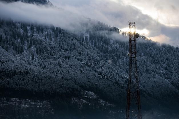 Schöner schuss eines funkturms auf einem schneebedeckten waldhintergrund