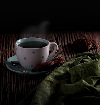 Schöner schuss eines heißen kaffees mit einem köstlichen paar kekse mit einem unscharfen hintergrund